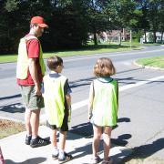 Kids with Partents getting prepared to cross an intersection